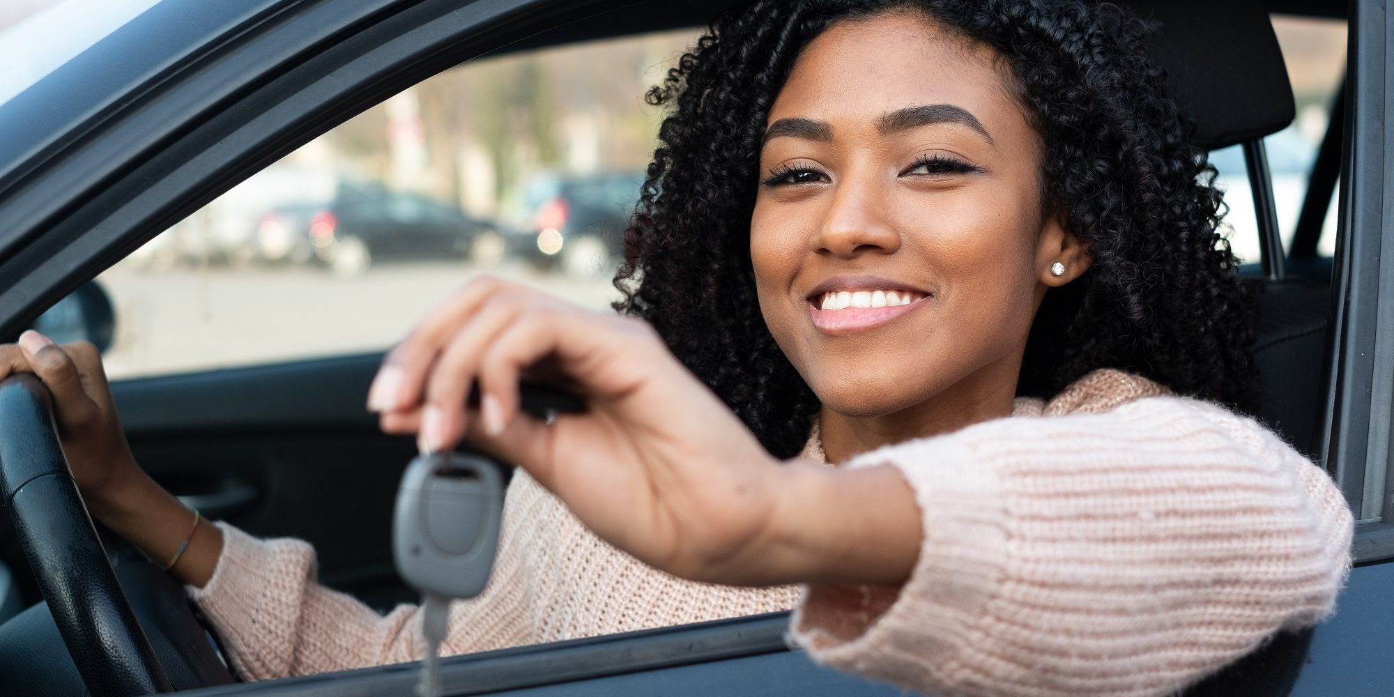 Happy young black woman seated in her new car